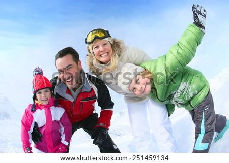 Cheerful family of 4 enjoying winter vacation - stock photo
