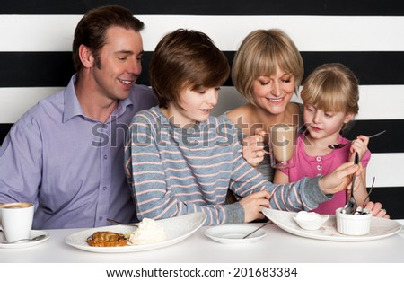 Cheerful family of four enjoying breakfast at a restaurant - stock photo