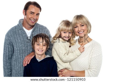 Cheerful family of four in warm clothing. Trendy winter outfits.