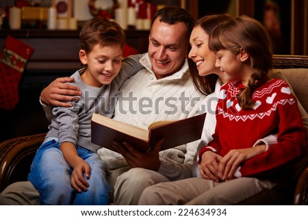 Cheerful family of four reading together on Christmas evening - stock photo