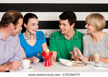 Cheerful family of four relishing delicious eatables and dessert. - stock photo