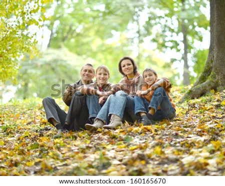 cheerful family of four resting on a hill in autumn - stock photo