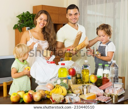Cheerful family of four with bags of food at home - stock photo
