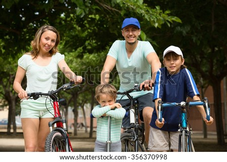 cheerful family of four with bicycles  walking in park