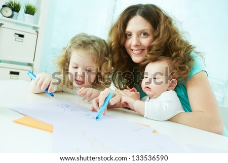 Cheerful family of three being occupied with drawing - stock photo