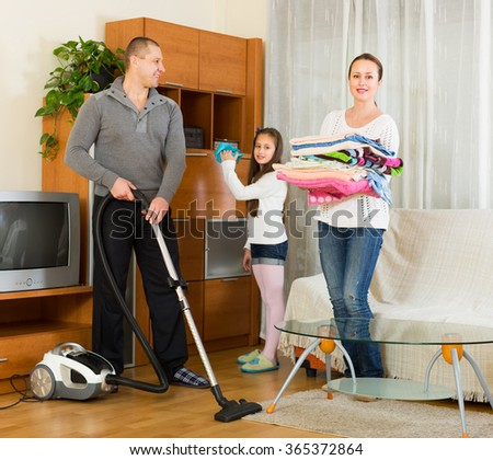 Cheerful family of three cleaning up at home all together. Focus on man