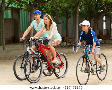 cheerful family of three cycling on city road in summer day - stock photo