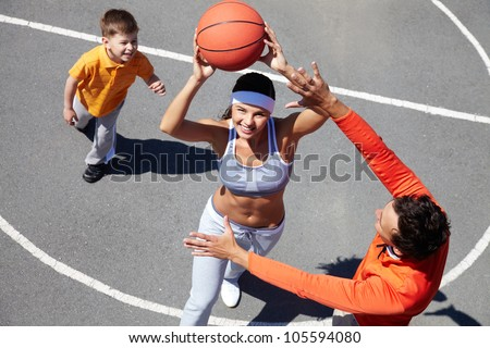Cheerful family of three playing amateur basketball - stock photo