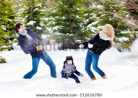 Cheerful family of three playing snowballs in the winter forest