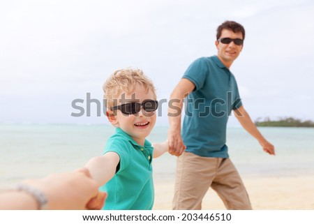 cheerful family of two having fun at the beach, vacation concept - stock photo