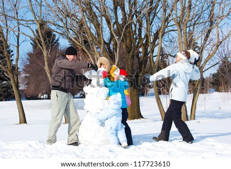 Cheerful family playing with snow - stock photo