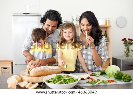 Cheerful family preparing lunch together in the kitchen - stock photo
