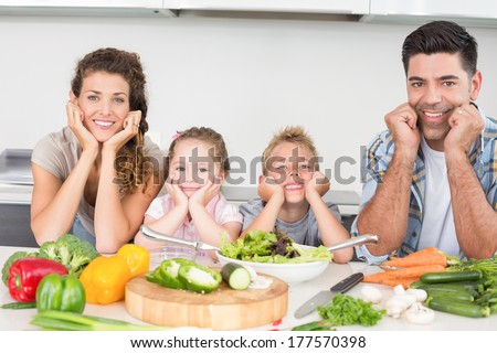 Cheerful family preparing vegetables together at home in kitchen - stock photo