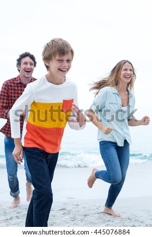 Cheerful family running at sea shore against sky - stock photo