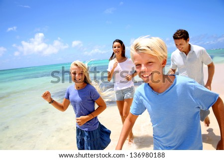 Cheerful family running on a sandy beach - stock photo