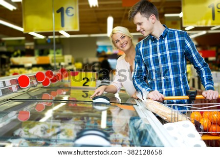 Cheerful family standing near display with frozen food in supermarket. Focus on the man - stock photo