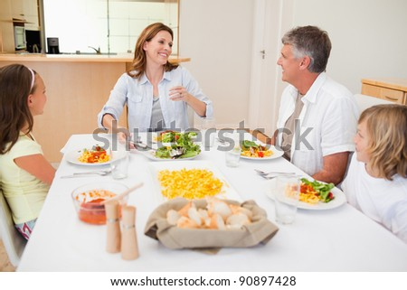 Cheerful family together at the dinner table - stock photo