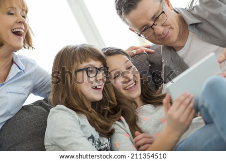 Cheerful family using tablet PC at home - stock photo