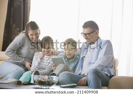 Cheerful family using tablet PC together in living room - stock photo