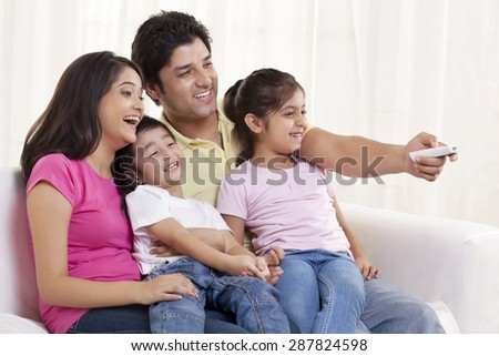 Cheerful family watching TV - stock photo