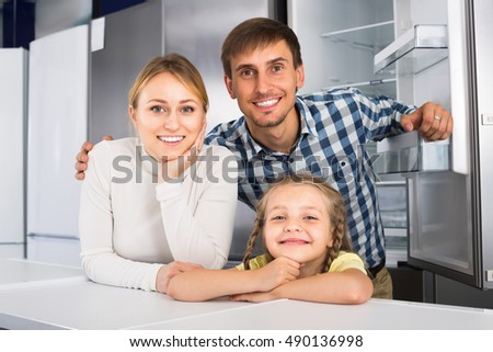 Cheerful family with child together in store with electronics