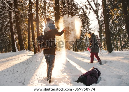 Cheerful family with daughter laughing in the forest and throwing snow. Focus on the woman