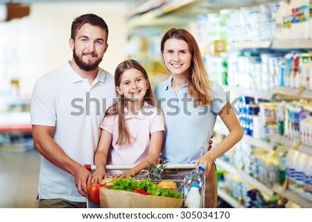 Cheerful family with shopping cart buying products