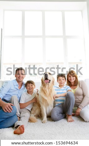 Cheerful family with their pet sitting on the floor at home - stock photo