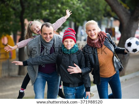 Cheerful family with two children spending free time outdoors - stock photo