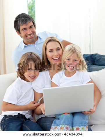 Cheerful family working at a computer sitting on sofa