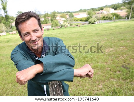 Cheerful farmer standing in country field - stock photo