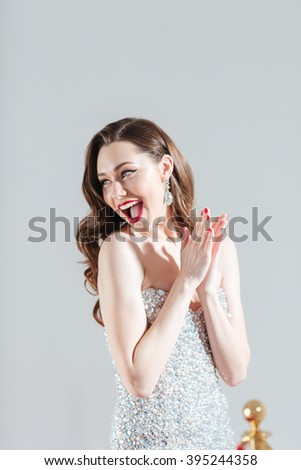 Cheerful fashion woman clapping hands isolated on a white background - stock photo