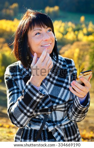 Cheerful fashion woman 40 years old wearing warm clothes in autumn. Beautiful brunette with autumn coat. Smiled and writing sms on her smartphone, Gold autumn background - stock photo