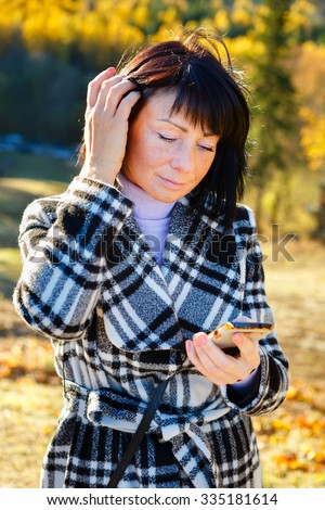 Cheerful fashion woman 40 years old wearing warm clothes in autumn. Beautiful brunette with autumn coat. Focus on her smartphone, reading sms. Gold autumn background - stock photo