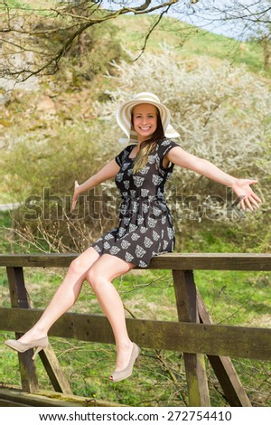 Cheerful fashionable woman in stylish hat and frock posing outdoor. Happy brunette girl with raised hands and smile. - stock photo