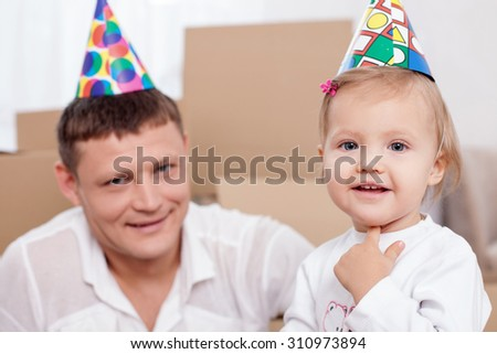 Cheerful father and her daughter are ready to move in another building. They are celebrating thus event. They are wearing holiday colored caps on their heads and smiling - stock photo