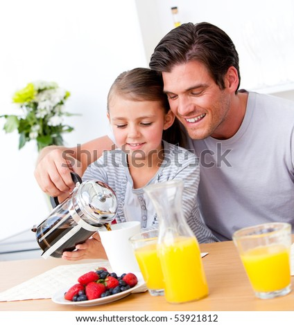 Cheerful father and his daughter having breakfast together in the kitchen - stock photo