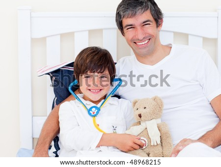 Cheerful father and his sick son playing with a stethoscope sitting on a bed