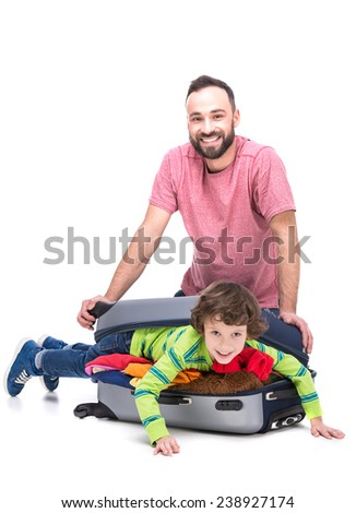 Cheerful father and his son in a suitcase, isolated on white background. - stock photo