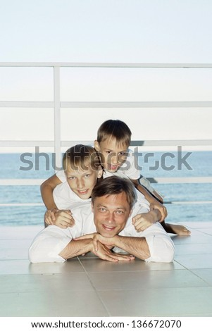 Cheerful father and his two young sons on vacation - stock photo