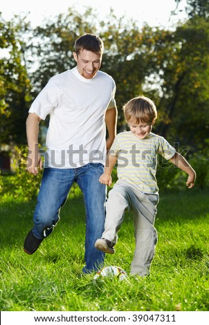 Cheerful father and son catch up with a football in park - stock photo