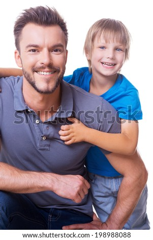 Cheerful father and son. Happy little boy embracing his father and smiling while both standing isolated on white - stock photo