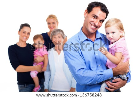 cheerful father holding his daughter with extended family on background - stock photo