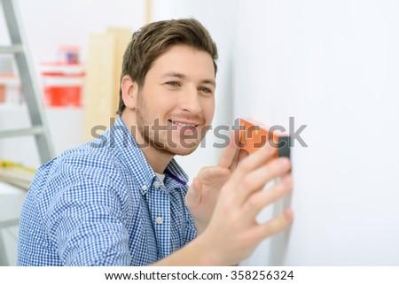 Cheerful father holding spirit level  - stock photo