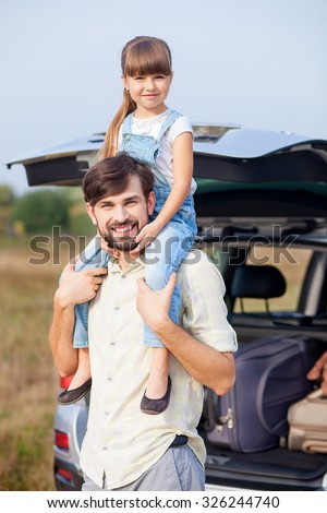 Cheerful father is holding his daughter on shoulders. He is standing near vehicle in the nature. They are looking at camera and smiling