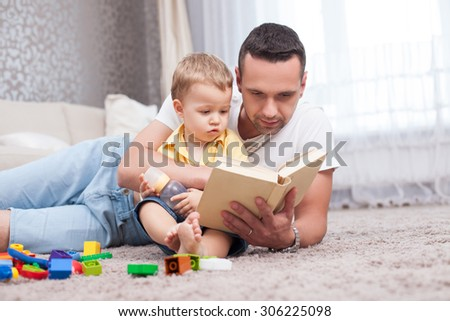 Cheerful father is lying on floor near his son and embracing him. The man is holding a book and reading to his child with concentration. The boy is sitting and listening attentively to his parent - stock photo