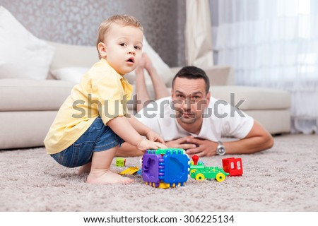 Cheerful father is lying on flooring near his son and smiling. They are playing with toys. They boy is sitting on a carpet and looking at the camera with interest - stock photo