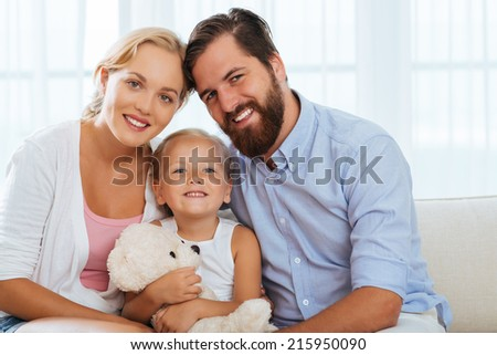 Cheerful father, mother and daughter sitting on the sofa in living room - stock photo