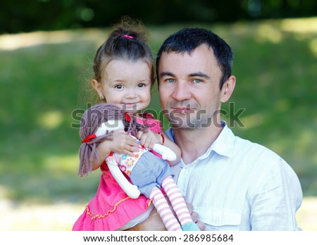 Cheerful father playing with his beautiful daughter - stock photo