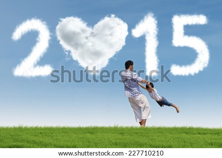 Cheerful father swing his son at field under cloud of 2015 - stock photo